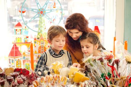 Jonge moeder haar zoon en dochter kiezen snoepjes in de snoepwinkel. Gelukkige kinderen plezier hebben