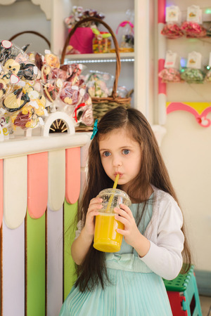 kids' room: Little girl drinking orange juice through straw and and sitting in the kids room Stock Photo