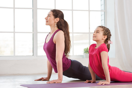 woman stretching: Young mother and daughter doing yoga exercise in fitness studio with big windows on background Stock Photo