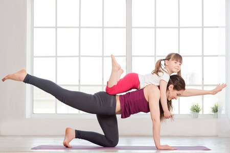 Young mother and daughter doing yoga exercise in fitness studio with big windows on background 스톡 콘텐츠