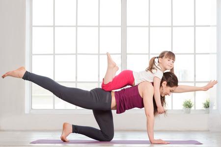 haciendo ejercicio: Joven madre y su hija haciendo ejercicios de yoga en el gimnasio con grandes ventanas en el fondo