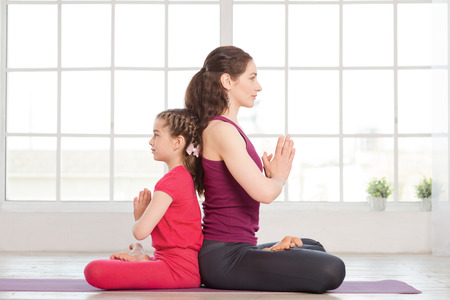 Young mother and daughter doing yoga exercise and sitting back to back in fitness studio with big windows on background