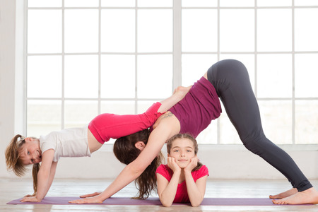 Young mother and daughters doing yoga exercise in home with big windows on background