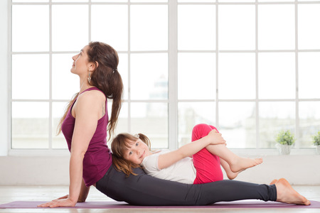 Young mother and daughter doing yoga exercise in fitness studio with big windows on background Stock Photo