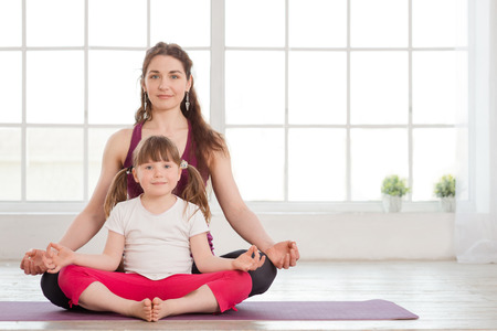 Young mother and daughter sitting in lotus position and doing yoga exercise in fitness studio with big windows on background