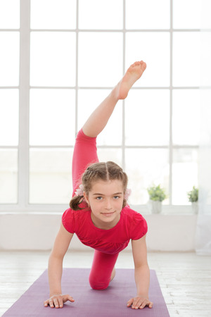 Little girl doing yoga exercise in fitness studio with big windows on background