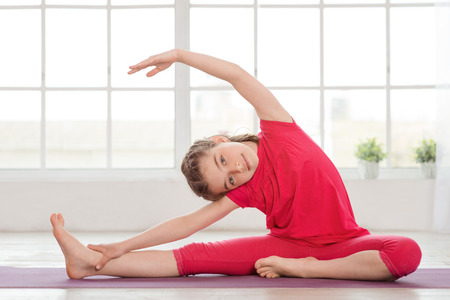 kid smiling: Little girl doing yoga exercise in fitness studio with big windows on background
