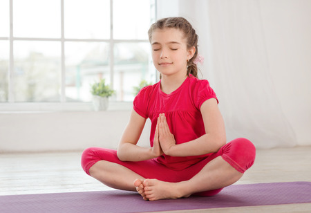 Little girl sitting in lotus position with closed eyes and hands up in fitness studio with big windows on background