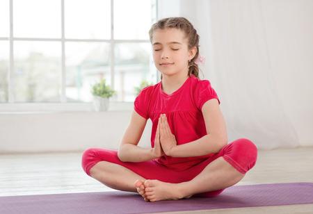 Meisje, zittend in lotushouding met gesloten ogen en handen in fitness-studio met grote ramen op de achtergrond