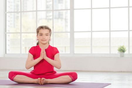 Meisje, zittend in lotushouding op fitness-studio met grote ramen op de achtergrond