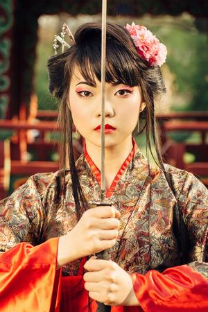 Mooie Koreaanse vrouw of geisha in kimono bedrijf samurai zwaard in de buurt van het gezicht