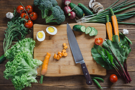 Cibo sano e ingredienti con il pomodoro, insalata, rucola, carote, barbabietola, barbabietola rossa, foglie, cetrioli, cipolla, verde, radicchio, funghi, aglio, broccoli, mezzo, uova e piselli su fondo rustico di legno, vista dall'alto