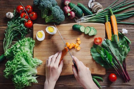 Gezonde voeding en ingrediënten met tomaat, sla, rucola, wortelen, biet, rode biet, bladeren, komkommer, ui, groen, radijs, champignons, knoflook, broccoli, de helft, ei en erwten op rustieke houten achtergrond, bovenaanzicht