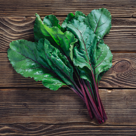 Close up of fresh beetroot leaves on rustic wooden background, top view