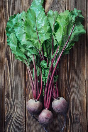 vegetable background: Close up of fresh beetroot leaves on rustic wooden background, top view