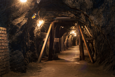 Long lighten tunnel through gypsum mine with wooden beams