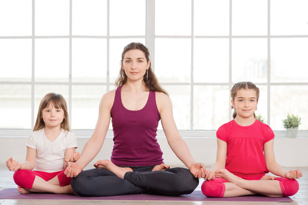 Young mother and daughters doing yoga exercise in fitness studio with big windows on background Imagens