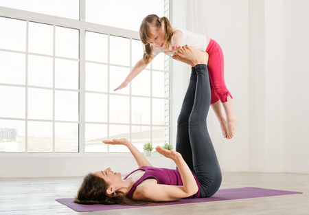 two woman: Young mother and daughter doing yoga exercise in fitness studio with big windows on background Stock Photo