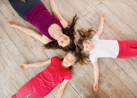 family with three children: Young mother and daughter lying on the floor after exercise and looking at camera. View from above