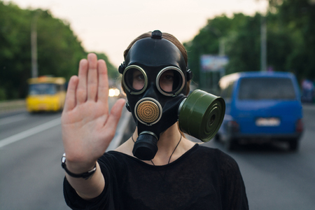 Ecological concept of air contamination. Woman in gas mask near highway showing stop gesture Imagens