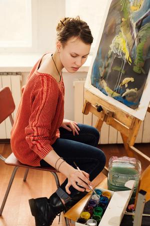 artistas: Hermosa mujer artista dibujando su foto sobre lienzo con colores al óleo en el estudio de arte en casa