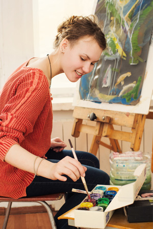 picture person: Smiling girl paints on canvas with oil colors in her workshop Stock Photo