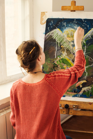 Beautiful woman artist drawing her picture on canvas with oil colors in her workshop
