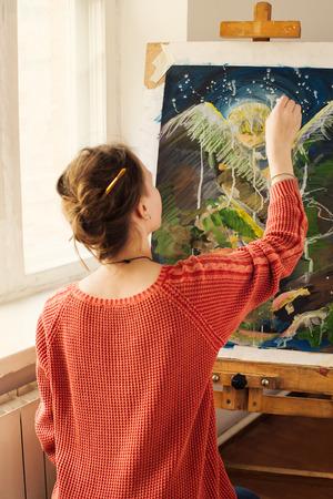 Mooie vrouw kunstenaar tekenen haar foto op canvas met olieverf in haar atelier Stockfoto