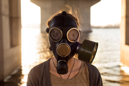 woman in water: Ecological concept of air contamination. Portrait of woman in gas mask near water