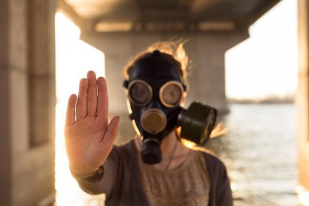 Ökologisches Konzept von Luftverunreinigungen. Frau in Gasmaske in der Nähe von Wasser zeigt Stop Geste