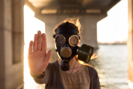 stop pollution: Ecological concept of air contamination. Woman in gas mask near water showing stop gesture Stock Photo