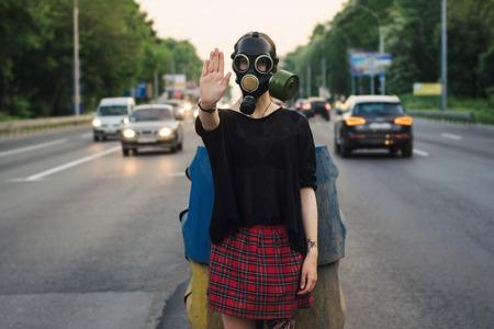 mascara de gas: Concepto ecológico de la contaminación del aire. Mujer en máscara de gas cerca de la carretera que muestra gesto de la parada