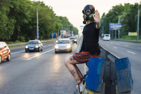 Ecological concept of air contamination. Woman in gas mask near highway showing stop gesture photo
