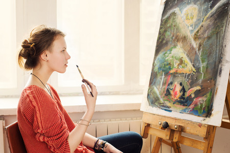 Beautiful woman artist drawing her picture on canvas with oil colors in home studio Imagens