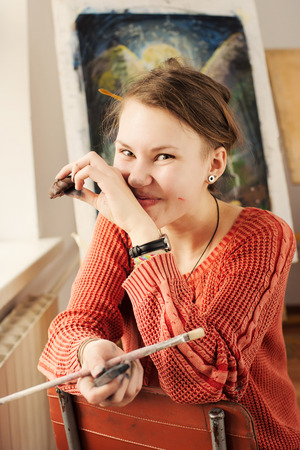 quirky: Portrait of beautiful woman artist with quirky expressions and touching her face in home art studio