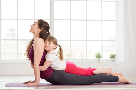 2 people at home: Young mother and daughter doing yoga exercise in fitness studio with big windows on background Stock Photo