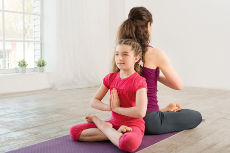 Young mother and daughter doing yoga exercise in fitness studio with big windows on background Imagens
