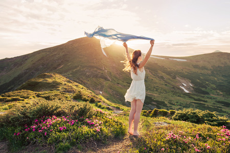woman flying: Woman feel freedom and enjoying the nature in the mountains with blue tissue in hands on sunset