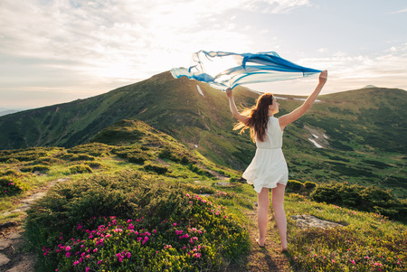 Woman feel freedom and standing on the mountain trail through blooming rhododendron valley with blue tissue in hands on sunset