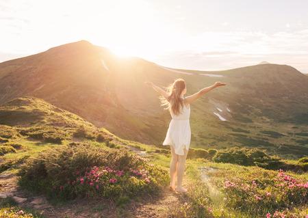 manos levantadas al cielo: Mujer feliz disfrutando de la naturaleza en las montañas y mirando en el cielo con las manos levantadas. Concepto de la libertad