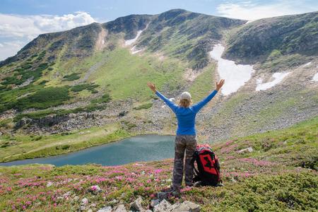 manos levantadas al cielo: Mujer siente la libertad y disfrutar de la hermosa vista de las montañas y mirando en el cielo con las manos levantadas Foto de archivo