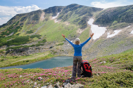 Vrouw voelt vrijheid en genieten van het prachtige uitzicht op de bergen en op zoek op de hemel met opgeheven handen