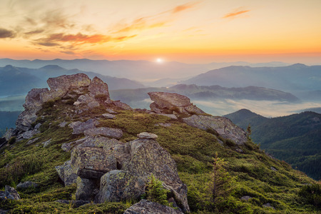 Beautiful view of foggy mountain landscape on sunset with big rocks on foreground in Carpathian mountains