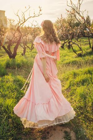 Aantrekkelijke vrouw in roze jurk genieten van de natuur en wandelen in de bloei tuin op zonsondergang. concept van de vrijheid