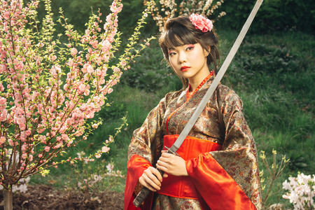 한국 여자 또는 기모노에서 얼굴 근처 사무라이 검을 들고 게이 샤
