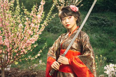 katana: Korean woman or geisha in kimono holding samurai sword near face Stock Photo