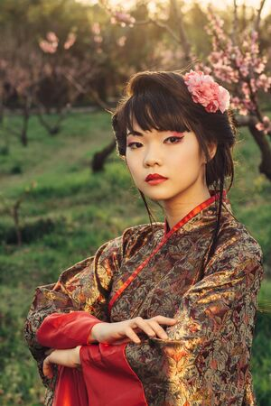 japanese people: Asian style portrait of young woman in the garden at sunset