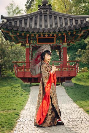 Mooie Aziatische vrouw die in de tuin en het dragen van traditionele Japanse kimono en rode paraplu Stockfoto