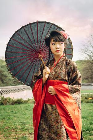 Mooie Aziatische vrouw die in de tuin en het dragen van traditionele Japanse kimono en traditionele paraplu