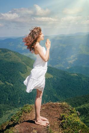 vestido blanco: Beautiful woman in white dress standing on the stone and pray Foto de archivo